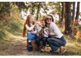 年轻的母亲带着女儿和儿子在森林里_7869930