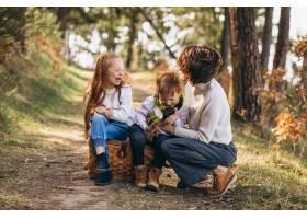 年轻的母亲带着女儿和儿子在森林里_7869931