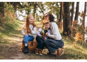 年轻的母亲带着女儿和儿子在森林里_7869932