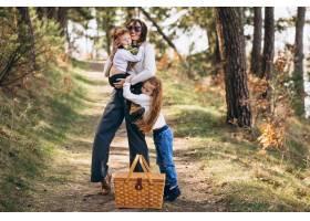 年轻的母亲带着女儿和儿子在森林里散步野餐_7869928