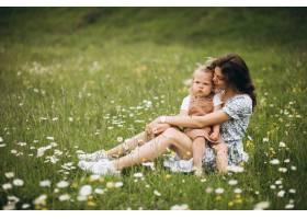 年轻的母亲带着小女儿坐在公园的草地上_8828231