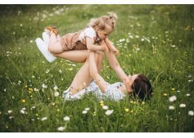 年轻的母亲带着小女儿坐在公园的草地上_8828244