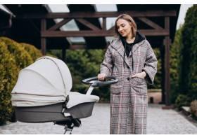 年轻的母亲推着婴儿车在公园里散步_7869617