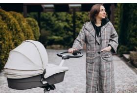 年轻的母亲推着婴儿车在公园里散步_7869625