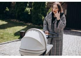 年轻的母亲推着婴儿车在公园里散步_7870145