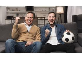 父子俩在客厅里看体育比赛_6881366