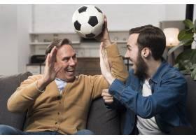 父子俩在客厅里观看体育比赛和欢呼_6881361