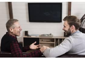 父子俩坐在沙发上的侧观_6608810