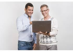 父子俩手持笔记本电脑的中景照片_6645645