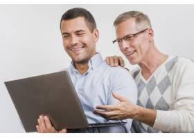 父子俩看笔记本电脑的前视图_6645643