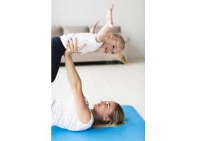 母亲在瑜伽垫上举起快乐女儿的侧观_7435924