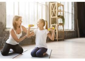 母亲帮助女儿在瑜伽垫上举重_7334103