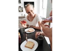 当他们吃早餐时迷人开朗的女人看着她的_6819633