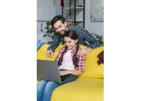 女儿在客厅里使用笔记本电脑_7069860