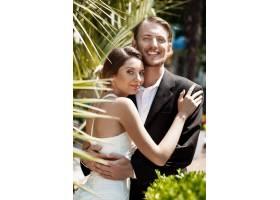 一对年轻漂亮的新婚夫妇微笑着在公园里拥_7599934