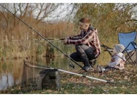 一个钓鱼的早晨父亲带着年幼的儿子在河边_7169660