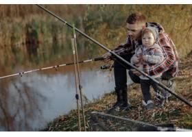 一个钓鱼的早晨父亲带着年幼的儿子在河边_7169662