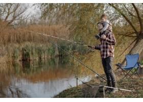 一个钓鱼的早晨父亲带着年幼的儿子在河边_7169663