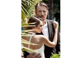 一对年轻漂亮的新婚夫妇微笑着在公园里拥_7599933