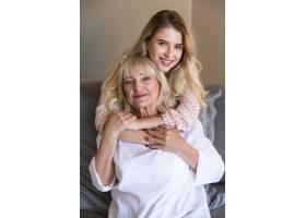 与孙女或女儿在沙发上拥抱的老年妇女_7339684