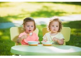 两个小女孩坐在一张桌子旁一起在绿色的草_7570444