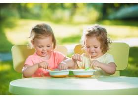两个小女孩坐在一张桌子旁一起在绿色的草_7570445