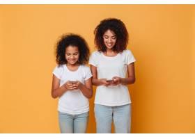 两个微笑的美国黑人姐妹拿着智能手机的肖像_6873851