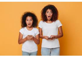 两个震惊的美国黑人姐妹拿着智能手机的肖像_6873853
