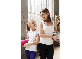 中景快乐的妈妈和女孩拿着瑜伽垫_7334146