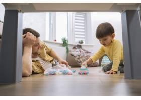 父子俩在起居室的桌子下面低低地看着_7496333