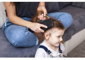 特写一位母亲在给女儿们做发型_7146651