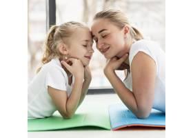 母亲在家与女儿在瑜伽垫上合影侧观_7435905