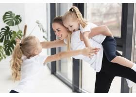 母亲在家中一边锻炼一边和女儿们玩耍_7435901