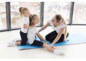 母亲在家中帮助女儿锻炼的侧观_7435891