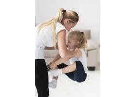 母亲在家中锻炼时抱起女儿的侧观_7435946