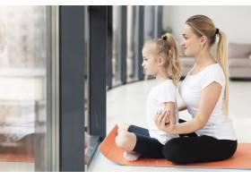 母亲在家和女儿一起做瑜伽的侧观_7435959