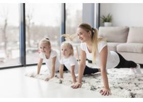 母亲在家和女儿一起锻炼的侧面观点_7435881