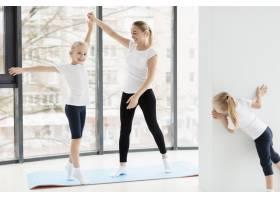 母亲在家和女儿们在瑜伽垫上锻炼_7435877