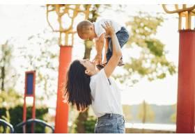 母亲带着年幼的孩子在操场上_7120800