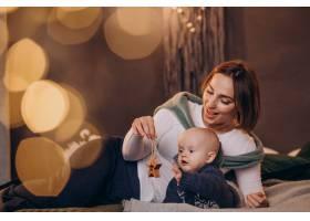 母亲带着她的男婴庆祝圣诞节_11981337
