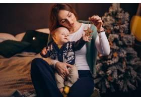 母亲带着她的男婴庆祝圣诞节_11981347