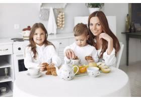 母亲带着孩子坐在厨房里吃饭_7121560