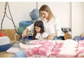 母亲带着年幼的女儿在工厂熨烫布料_6633989
