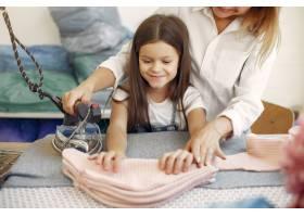 母亲带着年幼的女儿在工厂熨烫布料_6634004
