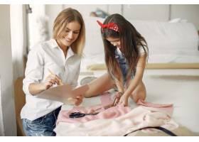 母亲带着年幼的女儿量一下缝纫用的布料_6633878