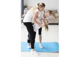 母亲锻炼时在家中陪女儿玩耍的侧观_7435914