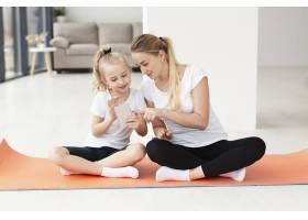 母女俩在家中坐在瑜伽垫上玩智能手机的前景_7435956