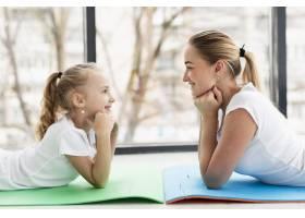 母女俩在家中瑜伽垫上摆姿势侧观_7435871