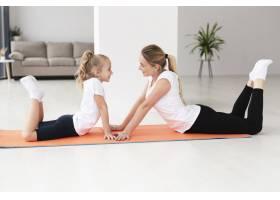 母女俩在家中瑜伽垫上锻炼侧观_7435902
