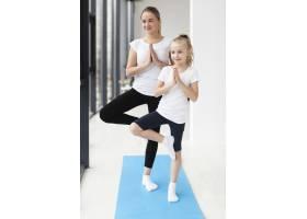 母女俩在家中练习瑜伽姿势的前景_7435944